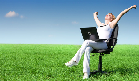 Excited blonde with a laptop in a meadow